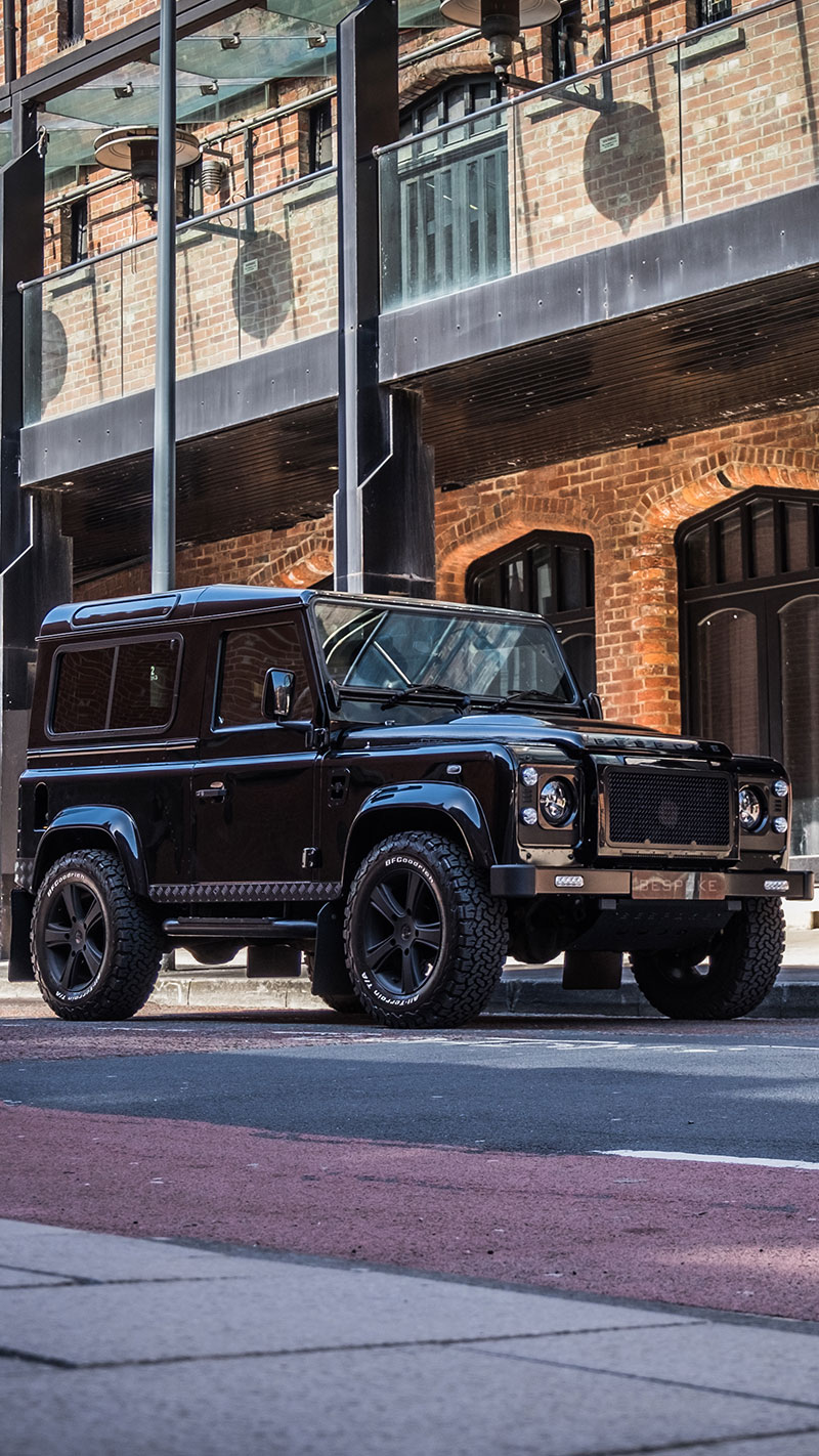 Black defender D90 parked on an urban street