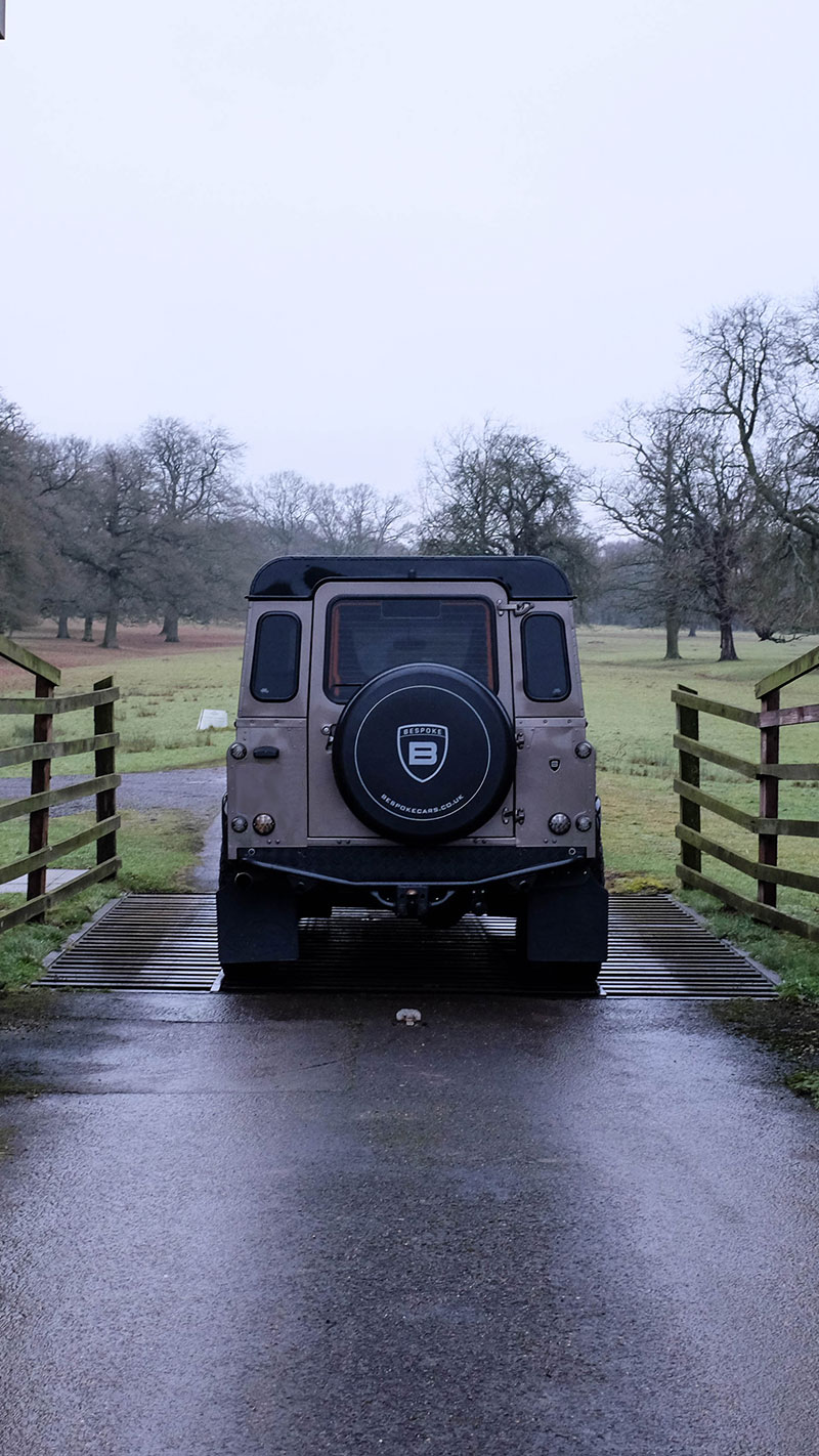 defender going across cattle grid on farm