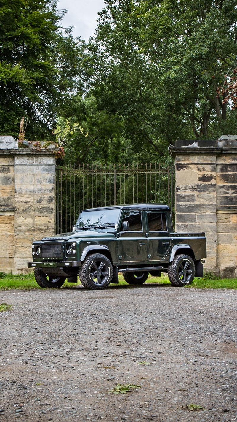 Green defender 110 pick up outside old estate gate