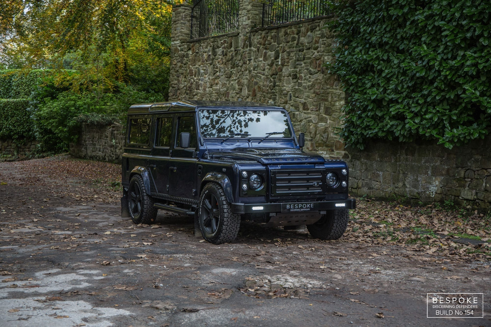 Blue defender 110 station wagon beside stone wall